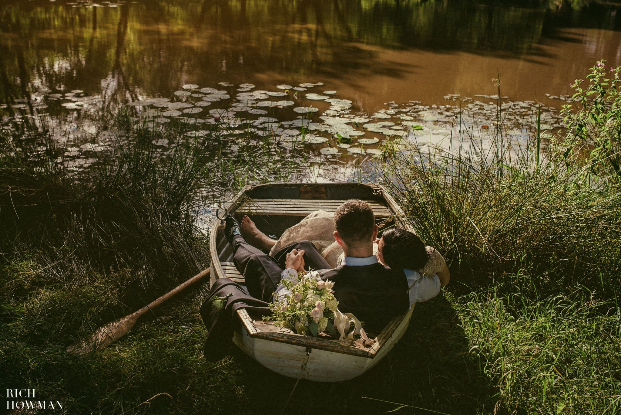 Photograph of the bride and groom by the lake during their wedding at Iscoyd Park.