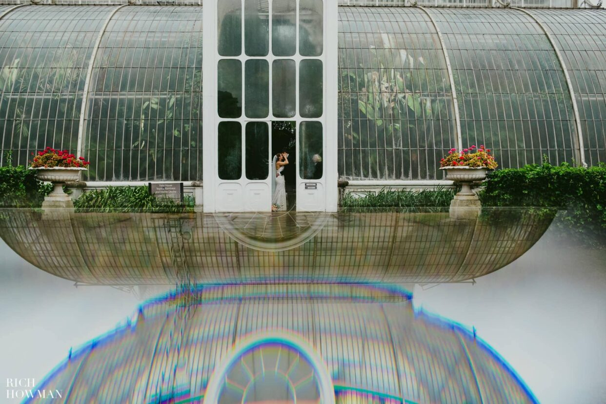 Bride and groom kissing in the doorway of the Palm House at the wedding at Kew Gardens.