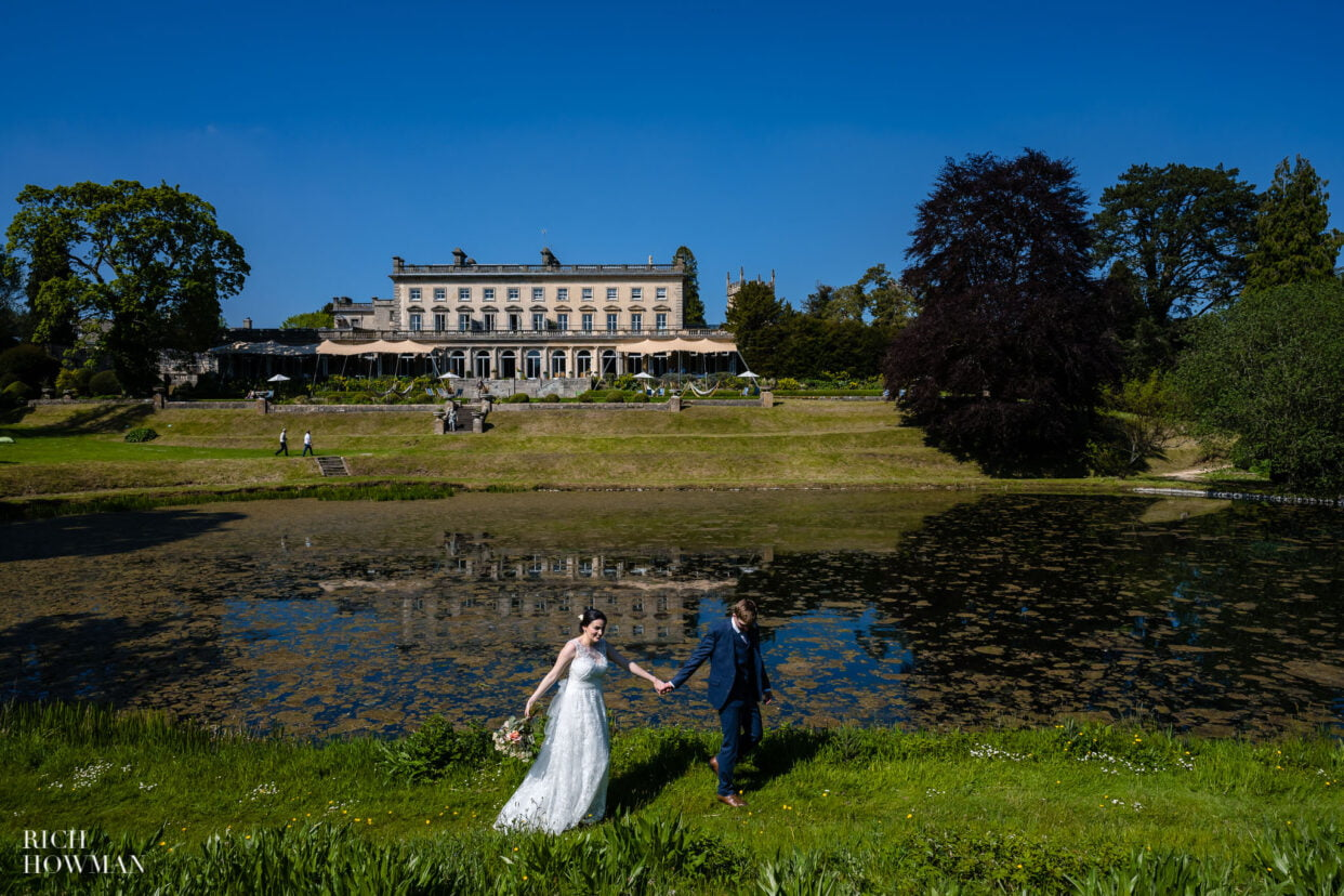 bride and groom next to lake in gardens of cowley manor