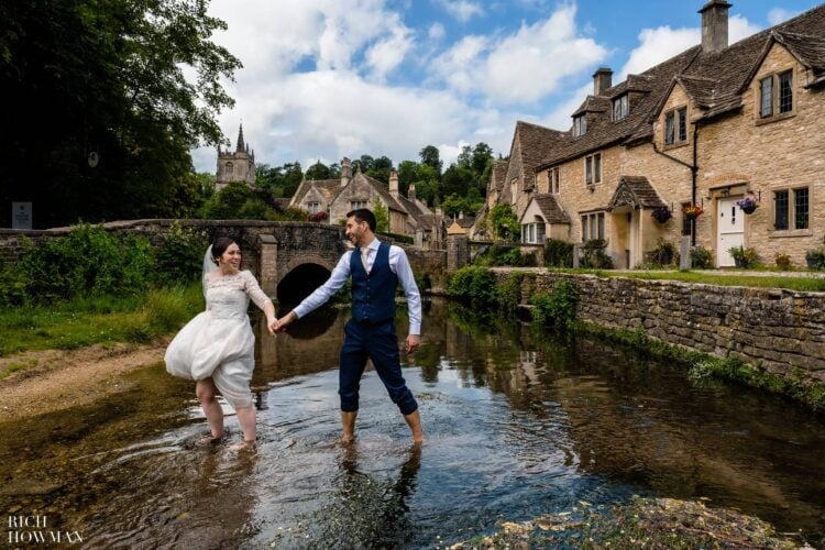 Bride and groom crossing river captured by Rich Howman, Castle Combe Wedding Photographer