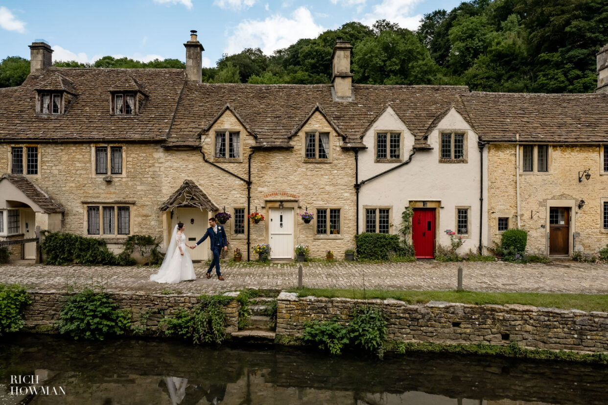 castle combe wedding photography bride and groom in front of cotswold stone houses