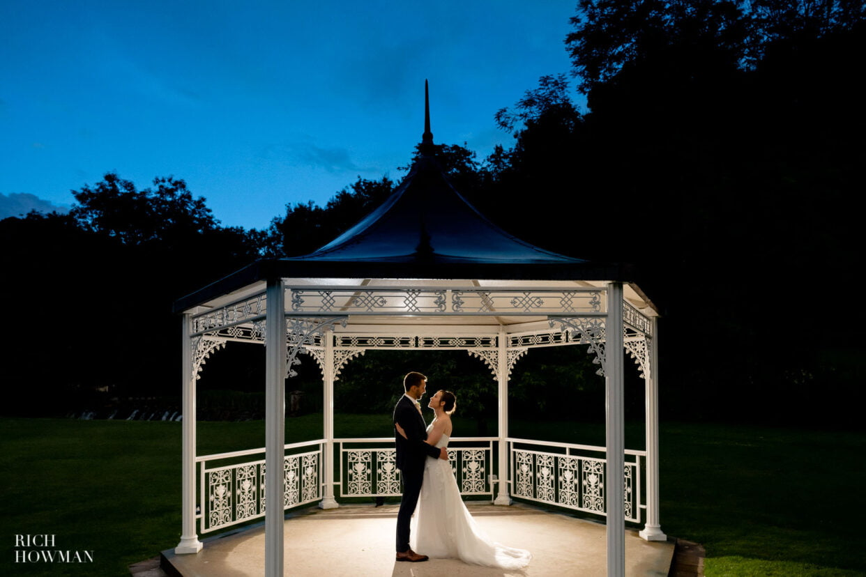 Manor House Castle Combe Wedding Photographer bride and groom in pergola bandstand